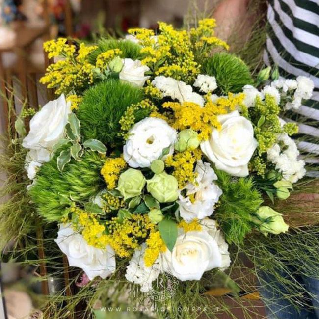 Donna Isabella Bouquet di fiori - dai toni tenui del bianco, verde e giallo: Rose Avalanche+, Lisianthus , Solidago, Green drick, accuratamente confezionato con verde decorativo di stagione.